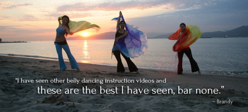 A group of women belly dancing on the beach with colorful silk veils